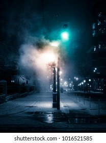 TORONTO WINTER SCENE - Steam/smoke covering downtown city traffic lights at night. Urban Toronto streets, with snow on ground and feeling of mystery. Toronto, Ontario, Canada.
