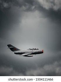 Toronto/Canada - August 30, 2019: Experienced pilot flying the MiG-15 Fighter Jet during the 2019 air show while executing dangerous maneuvers at high speed on a dark rainy day.