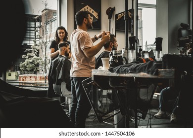 Toronto/Canada - June 15, 2019: Vintage scene inside a modern barbershop - Low angle perspective on barbers