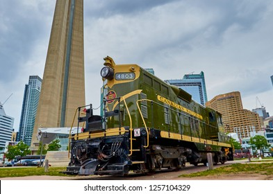 TORONTO,CANADA - JUNE 16 2016: Old train at the National Rail Museum against the tallest building in Canada. The museum is across the CN tower and its a major tourist attraction.
