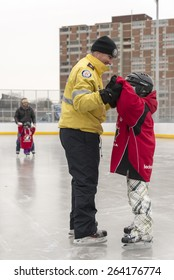 TORONTO,CANADA-JANUARY 3,2015:Toronto Police members partake in the official opening of the Regent Park ice rink; they served the community helping children in learning skating skills