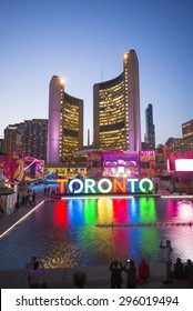 TORONTO,CANADA-JULY 9,2015: The new Toronto sign in Nathan Phillips Square celebrating the PanAm games, the New City Hall at back. Stage have been mounted to held a constant party called Panamania
