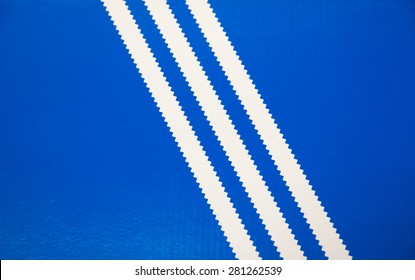 TORONTO,CANADA-MAY 2,2015: Old Adidas logo consisting in three white stripes on a blue background, shoebox lid. Adidas is a German producer of sportwear
