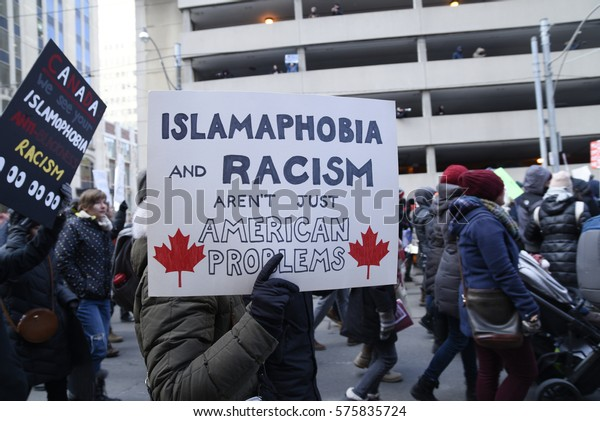 TORONTO-FEBRUARY 4:People with posters rejecting racism & Islamophobia during a protest in front of the US Consulate to denounce Trump's immigration policies on February  4,2017 in Toronto, Canada.