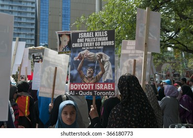 TORONTO-JULY 11: dA Muslim girl looking on as the elders gather around her to listen to the speakers uring the Al-Quds day rally on July 11, 2015 in Toronto,Canada.