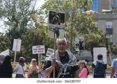 TORONTO-JULY 11: A Muslim man holding pictures of killed infants who allegedly are being described as terrorists by Israel during the Al-Quds day rally on July 11, 2015 in Toronto,Canada.