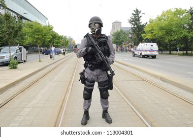 TORONTO-JUNE 27:  An elite police officer patrolling the street car tracks wearing gas masks during the G20 Protest on June 27, 2010 in Toronto, Canada.