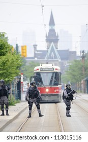 TORONTO-JUNE 27: Police personnel with gas masks protecting the street cars from getting vandalized during the G20 Protest on June 27, 2010 in Toronto, Canada.