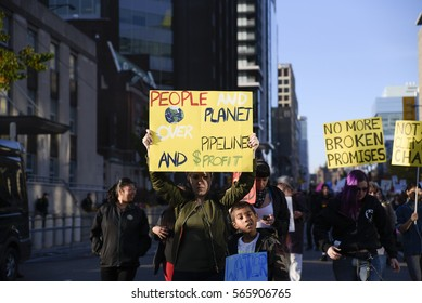 TORONTO-NOVEMBER 5:A woman with her son with a sign urging to prioritize plaanet over profit during a solidarity rally with the Dakota Access Pipeline protesters on November 5, 2016 in Toronto,Canada.