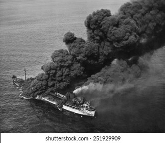 A torpedoed American tanker burning after an Axis submarine attack. Crew members brought the fire under control and the ship was towed to port for repair. Ca. 1942-43. World War 2.