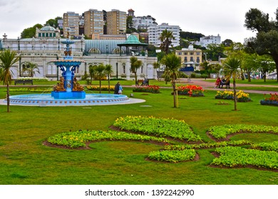 Torquay, Devon / England - 5/3/2019: The pretty and ornate fountain at the centre of the formal Princess Gardens on the promenade at Torquay on the English Riviera. The Pavilion is in the background.