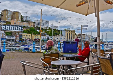 Torquay, Devon / England - 5/3/2019: A street view across the inner harbour/ marina at Torquay with yachts at moorings. A couple relax outside enjoying a coffee together, and the picturesque setting.