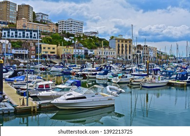 Torquay, Devon / England - 5/3/2019: A street view across the inner harbour/ marina at Torquay with yachts at moorings. Calm still waters with reflections of boats and buildings on the hillside behind