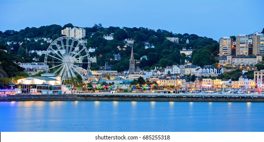Torquay Promenade at dusk taken from a distance, showing the promenade illuminated with colourful lights that are reflecting in the calm sea. Devon, England