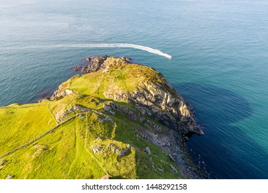 Torr Head headland, rocky cliff and peninsula in County Antrim, Northern Ireland, near Ballycastle. Aerial photo with a motorboat