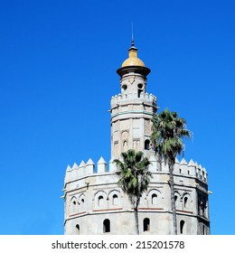 Torre del Oro in Seville (Spain) with two palm trees in front against a clear blue sky