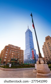 Torre Latinoamericana or tower of Latino America and other buildings and Mexican flag on Juarez avenue and morning sun flare, Mexico city capital