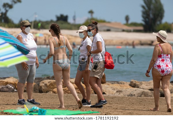 Torrenostra, Castellon, Spain - July 16, 2020: Beach assistants and attendants, work on the beach informing to help beachgoers to prevent the spread of the COVID-19 during the Coronavirus pandemic.