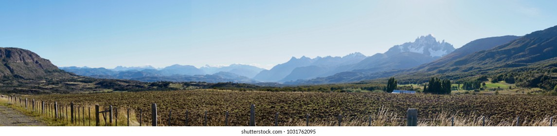 Torres del Paine National Park landscape panorama. An immaculate sky hangs over the breathtaking Andes and plant life below. A diverse landscape of grass, trees, water, and mountains.