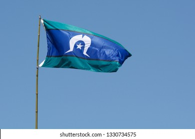Torres Strait Islander Flag wave against blue sky in Australia. The Torres Strait Islander Flag represents Torres Strait Islander people.