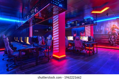 Torrevieja, Spain - April 15, 2021: Inside of empty internet cafe, glow neon illuminated cybercafe room with computers on tables, no people. Modern place for gamers, computer game compete, fun concept