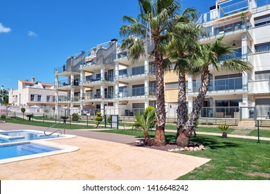 Torrevieja, Spain - April 24, 2019: High rise residential multi-storey house, closed urbanization with swimming pool area for sunbathing, no people. Alicante province, Costa Blanca, Torrevieja, Spain
