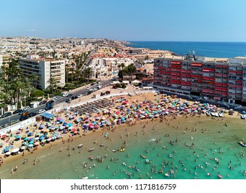 Torrevieja, Spain - August 23, 2018: Aerial panoramic view of beach and Torrevieja cityscape. People, tourist sunbathing and swimming on the sandy beach of Los Locos at summertime. Costa Blanca, Spain