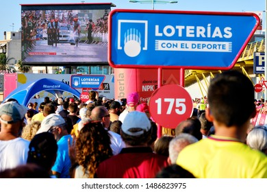 Torrevieja, Spain - August 24, 2019: Lot of people unrecognizable spectators during La Vuelta international cycling watching race on television broadcast on big screen outdoors, Torrevieja, Spain
