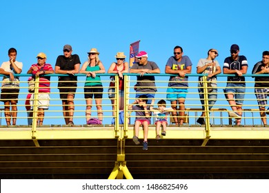 Torrevieja, Spain - August 24, 2019: Lot of spectators gathered together on bridge against blue sky for watching La Vuelta, one of the leading international cycling races starting in Torrevieja city