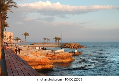 Torrevieja, Spain - February 17,  2018: People walking by the seafront of Torrevieja at sunset. Costa Blanca. Spain