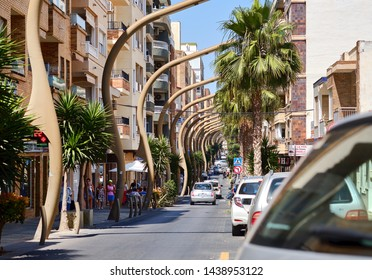 Torrevieja, Spain - June 10, 2019: Busy Caballero de Rodas street Torrevieja resort town unusual bended street lights along the urban road in the center of city, lush palm trees walking people, Spain