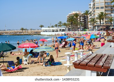 Torrevieja, Spain - June 10, 2019: Lot of tourists enjoy warm summer day in the sandy beach of Playa Del Cura, holidaymakers under sun umbrellas relaxing, swimming in the sea. Costa Blanca, Spain