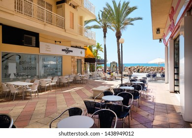 Torrevieja, Spain - May 16, 2019: Charming empty street with tables and chairs open-air outdoors cafe and restaurants Mediterranean Sea view, Torrevieja resort, Costa Blanca, Province Alicante, Spain