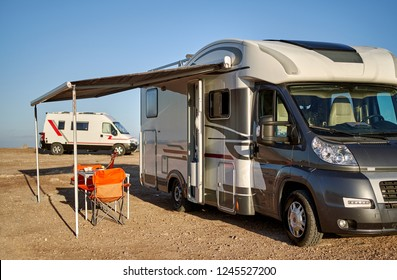 Torrevieja, Spain - November 11, 2018: Empty folding chairs and table under canopy near new modern recreational vehicle camper trailer. Adventure, active people traveling by motor home concept