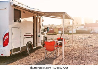 Torrevieja, Spain - November 11, 2018: Empty folding chairs and table under canopy near recreational vehicle camper trailer. Adventure, active people traveling by motor home concept