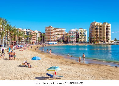TORREVIEJA, SPAIN - NOVEMBER 13, 2017: People enjoying and sunbathing at the Playa De Los Locos beach.