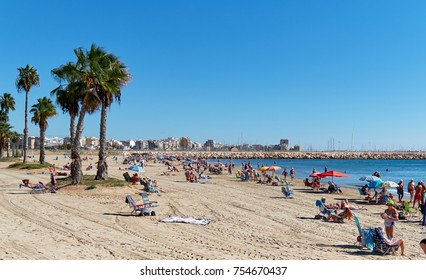 Torrevieja, Spain - October 20, 2017: Naufragos beach in the Torrevieja resort city. Torrevieja is a Mediterranean city, popular travel destination for tourists. Costa Blanca. Spain