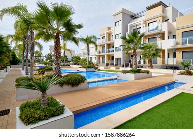 Torrevieja, Spain - October 28, 2019: Modern apartments with swimming pool cozy decorated leisure area, sunny warm day. Real estate purchasing, loan mortgage, new dwelling concept