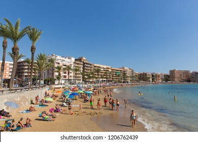 TORREVIEJA, SPAIN-OCTOBER 6th 2018: Beautiful October sunshine and hot weather drew people to the sandy beach at Torrevieja, Spain on Saturday 6th October 2018