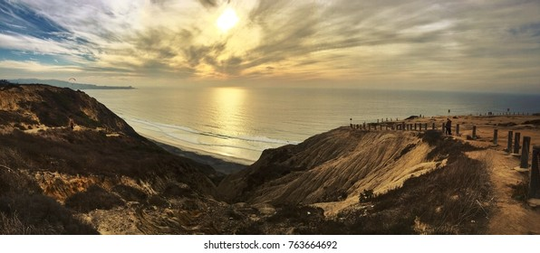 Torrey Pines lookout over the Pacific Ocean during sunset.  The clouds show a dazzling display of colors as the sun shines through them brightly.