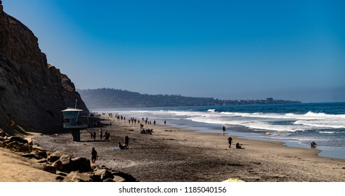 Torrey Pines State Beach on a beautiful, summer day with waves, people sand, surf, sunbathing, umbrellas,