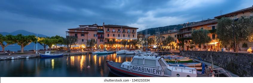 TORRI DEL BENACO, ITALY - JUNE 28, 2014: The port of Torri del Benaco at evening, small village on the coast of Lake Garda (lago di Garda) , Veneto, Verona, Italy, Europe