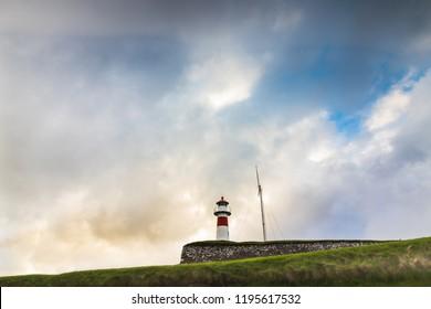 Torshavn / Faroe Islands - June 16 2017: Lighthouse in Torshavn, the capital of Faroe Islands during sunset in summer with clouds in the sky.
