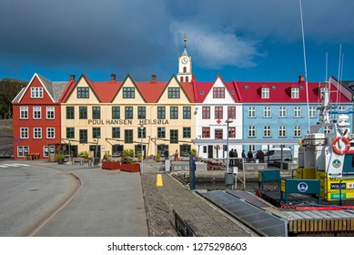 Torshavn, Faroe – July 11, 2018  Gabled buildings along the quayside in Vestaravag harbor in Torshavn, the tp of the cathedral with its clock is in the middle