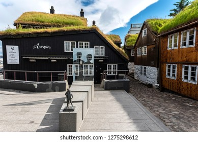 Torshavn, Faroe – July 11, 2018  Aarvegur Street view in harbor quartiers of Torshavn city, modern sculptures in the middle of the old traditional building facades and  grass roofs