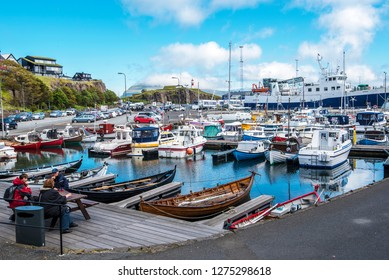 Torshavn, Faroe – July 11, 2018 People sitting at the terrace of Torshavn Port . Boats, yachts and the ferry are in the port, Skansin and city houses are at background