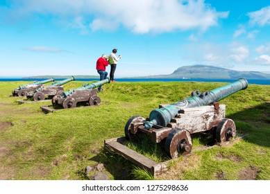 Torshavn, Faroe – July 11, 2018   Tourist photographing Faroese landscape from Skansin, historical fortress in Torshavn, old cannons are at foreground and Nolsoy island at background