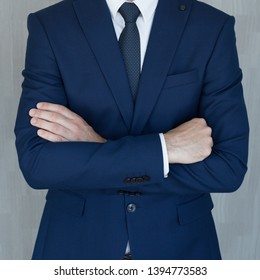 Torso of anonymous businessman standing with hands in lowered steeple wearing beautiful fashionable classic grey suit, white shirt and blue tie, against grey backgound.