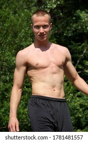 Torso of athlete in black underwear on a green nature background
