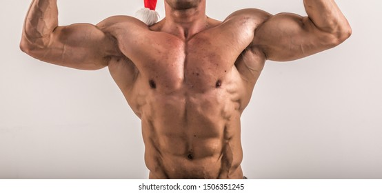 torso of attractive male body builder on blue background. Bodybuilder flexing his muscles in studio